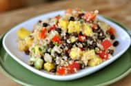 white plate with quinoa salad full of mangoes, tomatoes, cucumbers, and black beans