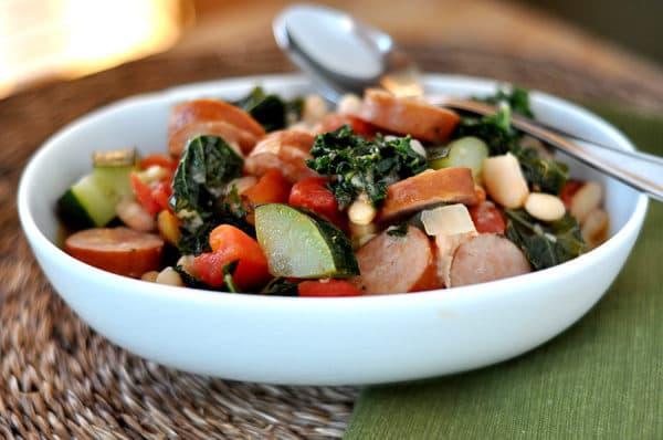 white oval bowl with sausage, kale, tomato, white bean, and zucchini ragout