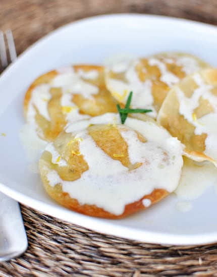 a white plate with four large ravioli drizzled with alfredo sauce
