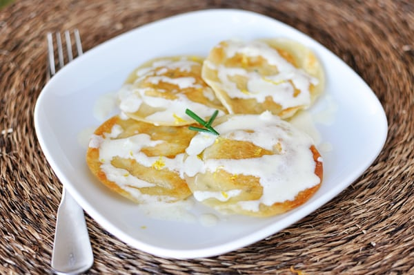 top view of a white plate with four large cooked ravioli drizzled with a white sauce