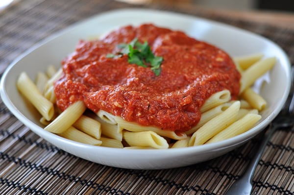 white bowl of cooked tube pasta smothered with red brie sauce
