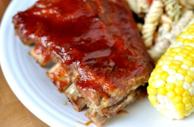 a rack of bbq ribs on a white plate with corn on the cob and a pasta salad