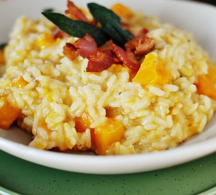 cooked butternut squash risotto in a white bowl, with crumbled bacon and sage leaves on top