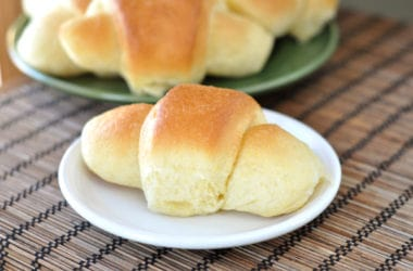 a white plate with a golden brown crescent roll with a green plate of more baked rolls behind it