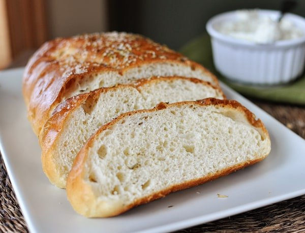 half a loaf of rosemary bread with two big slices in front of the loaf, on a white rectangular plate
