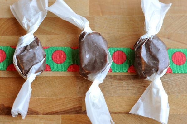 three parchment wrapped chocolate caramels on top of a red and green ribbon
