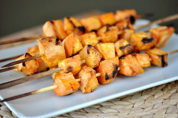 side view of a white platter with grilled sweet potato skewers