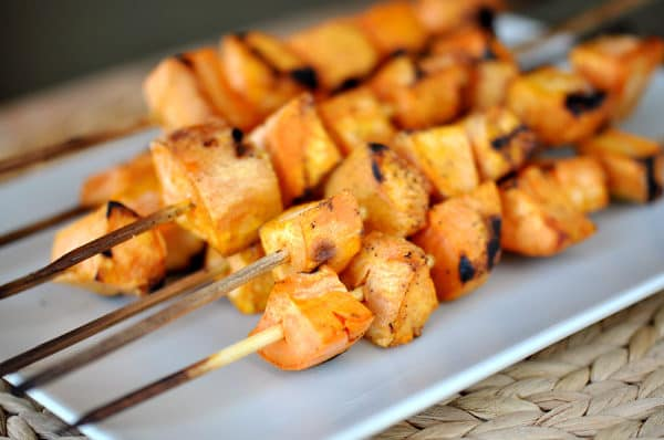 rectangular white platter with grilled sweet potato skewers