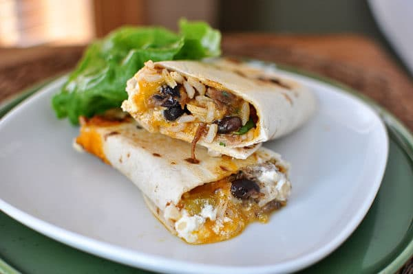 A griddled, rolled up tortilla sitting on a white plate, filled with southwest ingredients.