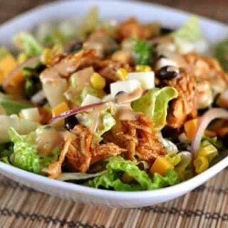 white bowl filled with salad, bbq chicken, corn, and slices of red onions