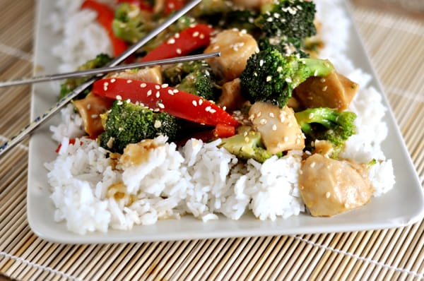 white platter with cooked white rice and sesame stir fry chicken