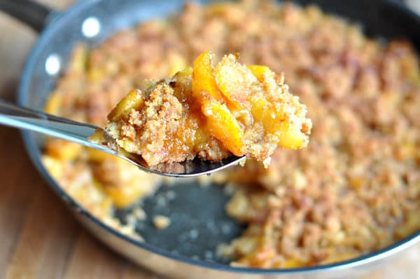 peach cobbler in a dark skillet with a scoop being taken out