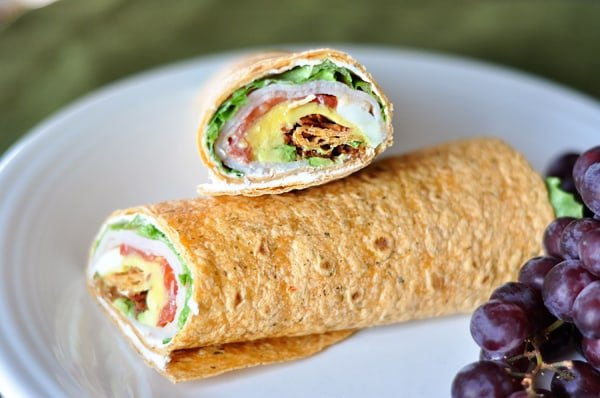 white plate with a turkey cobb wrap filled with veggies and turkey and cut in half next to purple grapes