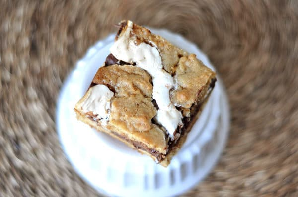 a cookie bar sitting on a white ramekin with ribbons of marshmallow and fudge inside the bar