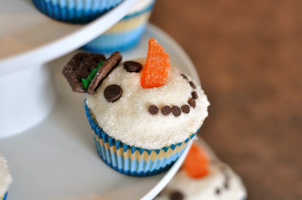 cupcakes decorated like snowmen on a cupcake tier