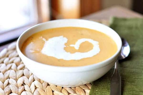 tomato soup in a white bowl with a swirl of cream in it