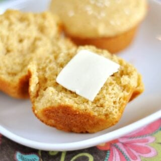 a muffin split in half with a pat of butter on one half