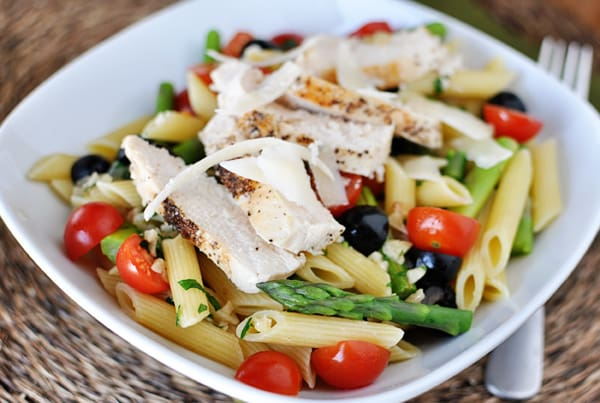 white bowl with cooked penne pasta, pieces of asparagus, cherry tomatoes, olives, and chicken slices