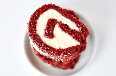 slices of a red velvet cake roll with a cream cheese filling stacked on a white plate