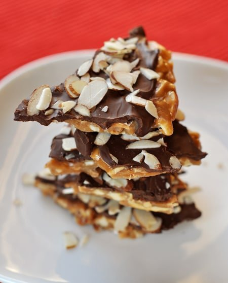 pieces of almond roca stacked on a white plate