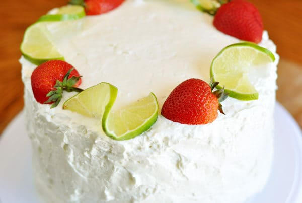 a white frosted cake on a white platter with ribbons of lime and full strawberries surrounding the top