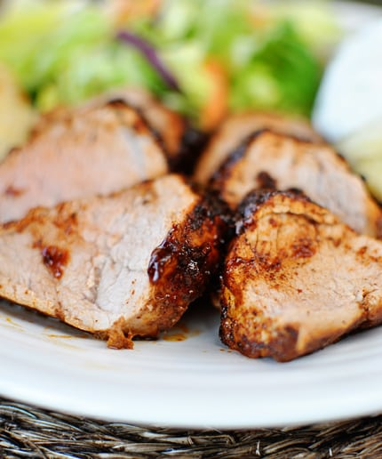 slices of seasoned pork tenderloin on a white plate with a salad in the background