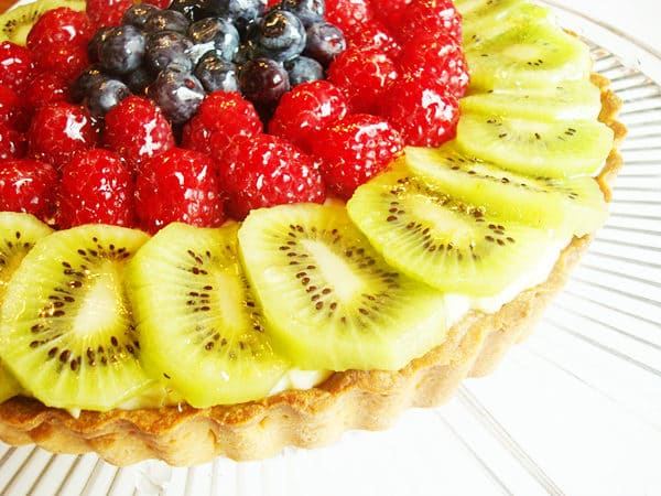 tart with frosting and fresh fruit on top
