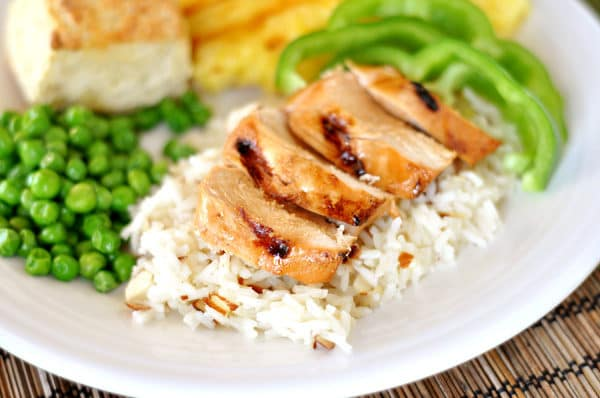 a white plate with white rice, chicken strips on top, green pepper slices, and green peas