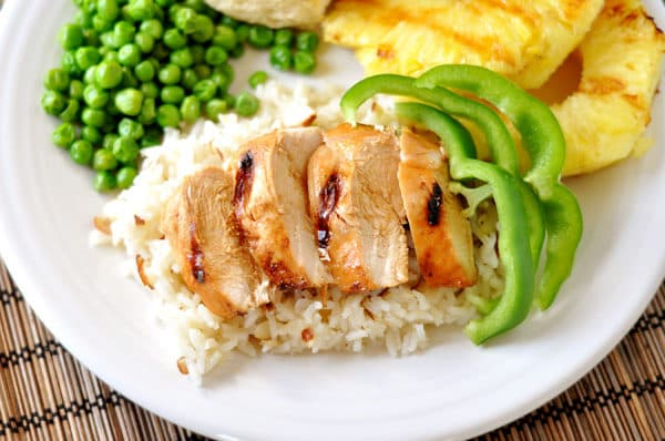 top down view of a white plate full of white rice with chicken slices on top, green pepper slices to the side, green peas, and grilled pineapple slices