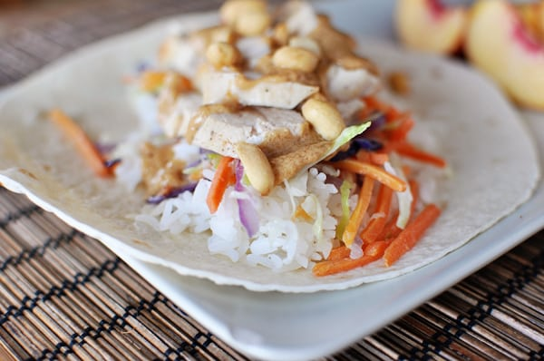 white tortilla topped with cooked rice, asian chicken, veggies, and peanuts stacked on top