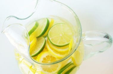 top view of a glass pitcher with lemon and lime slices and clear punch