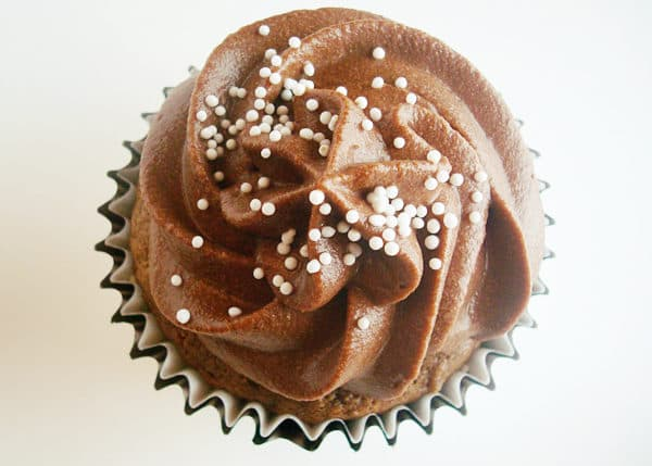 top view of a chocolate frosted cupcake with white sprinkles