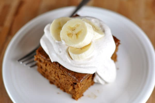 top view of a piece of brown gingerbread cake topped with whipped cream and sliced bananas