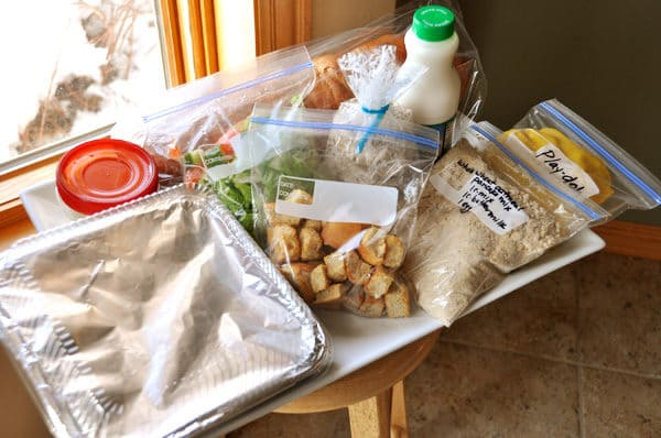a big white tray full of various bagged foods and sides to use as a take-in meal