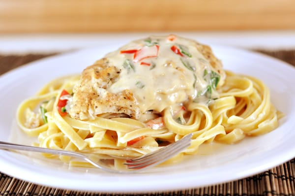 A plate full of cooked fettuccine noodles, with a breaded chicken breast, white sauce, and green and red peppers on top.
