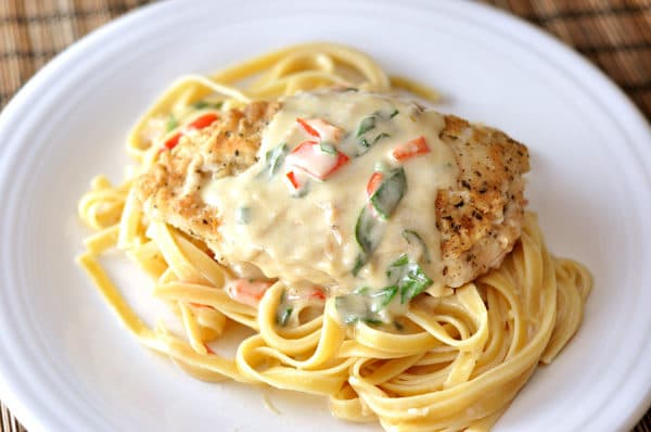 top down view of a white plate with cooked fettuccine, a breaded chicken breast, and a pepper cream sauce