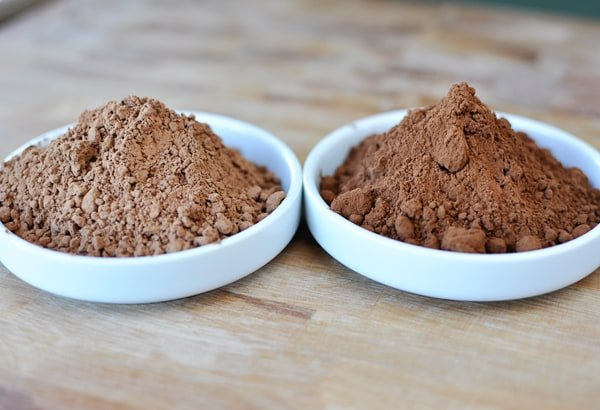 two small white bowls of baking cocoa next to each other