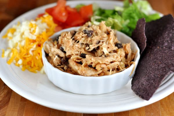 shredded chicken and black beans in a white ramekin with cheese, tomatoes, lettuce and chips surrounding it