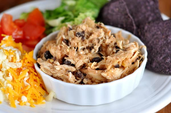 small white ramekin with shredded chicken and black beans on a plate surrounded with toppings