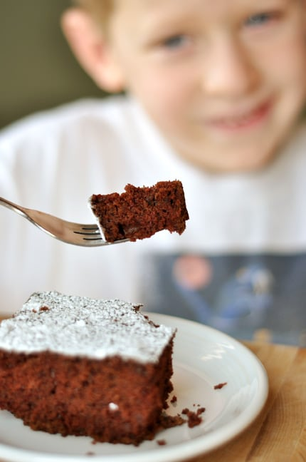 a piece of powdered sugar dusted cake with a little boy behind it holding a bite of the cake on his fork
