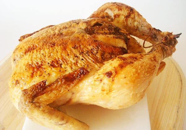 whole roasted chicken on a white cutting board