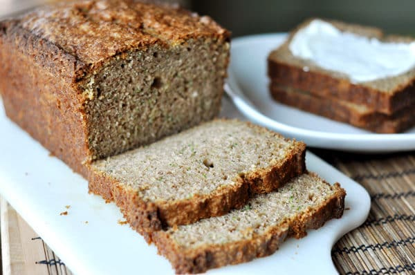 A loaf of zucchini bread with two slices cut off.