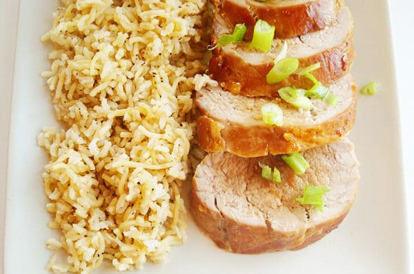 sliced pork tenderloin next to brown rice on a white platter
