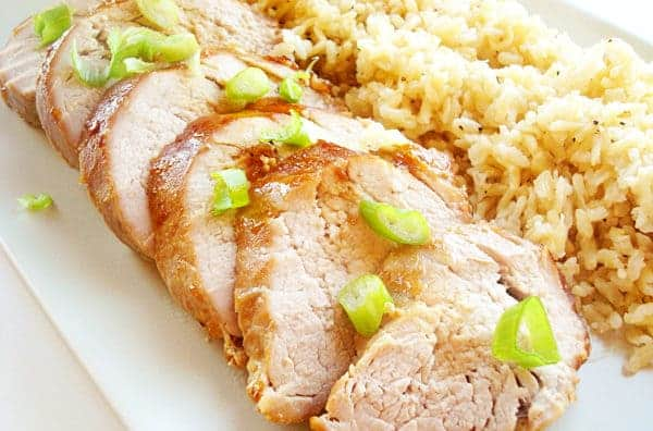 sliced pork tenderloin and brown rice on a white platter