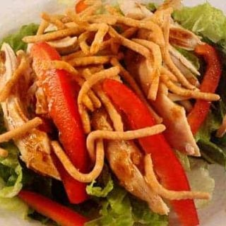 chicken, pepper strips, and chow mein noodles on a bed of green lettuce