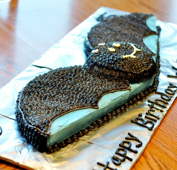 a frosted cute, black bat cake on a tinfoil covered cake board