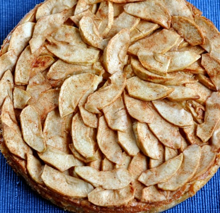 top view of a circular apple torte with cooked apples lining the top