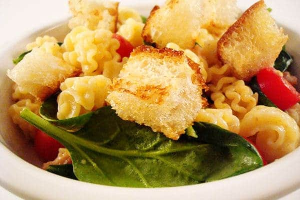 white bowl with spinach, pasta, and croutons