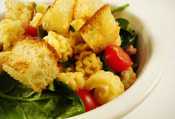 white bowl with tomatoes, pasta, spinach, and croutons