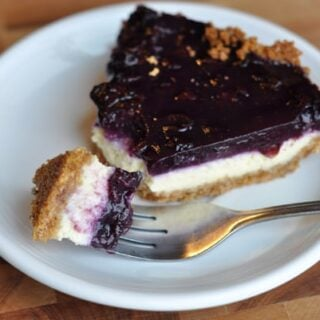 slice of cheesecake with blueberry topping and a bite being taken out with a fork